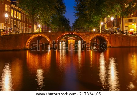 Night city view of Amsterdam canals and seven bridges, Holland, Netherlands.