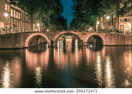 Night city view of Amsterdam canals and seven bridges, Holland, Netherlands.. Toning in cool tones - stock photo