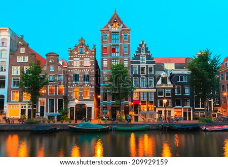 Night city view of Amsterdam canals and typical houses, boats and bicycles, Holland, Netherlands.  - stock photo