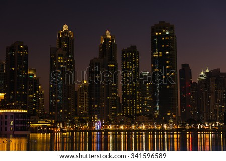 Night cityscape of Dubai city, United Arab Emirates. Reflections in the water - stock photo
