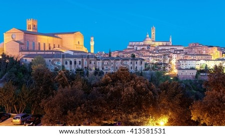Night cityscape of Siena, a beautiful medieval town in Tuscany Italy, with view of the Dome & Bell Tower of Siena Cathedral ( Duomo di Siena ), landmark Mangia Tower, and Basilica of San Domenico  - stock photo