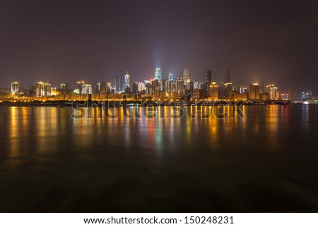 Night cityscape with skyscrapers, reflecting in the river. Chongqing, China - stock photo