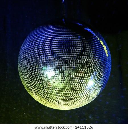 night club lighting yellow mirror-ball over black - stock photo