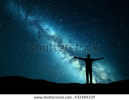 Night colorful landscape with green Milky Way and silhouette of a happy man with raised up arms on the hill. Beautiful Universe. Travel background with starry sky.  - stock photo