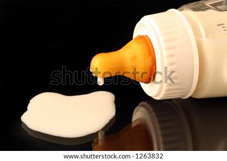 night feeding - a fallen baby bottle dripping milk / formula over black background - stock photo