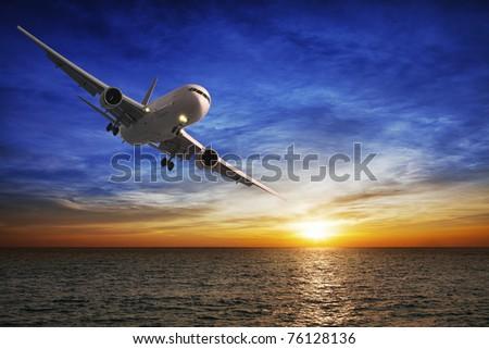 Night flight. Jet aircraft over the sea at dusk. - stock photo