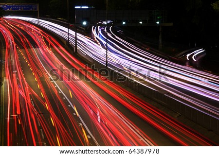Night highway (Cars in a rush moving fast on a highway (speedway) . - stock photo