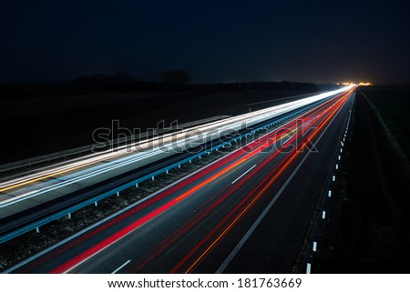 Night highway with car traffic and blurry lights when long exposure - stock photo