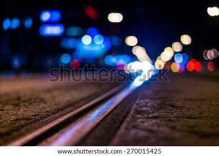 Night highway with rails, cars go over it. View from the level of asphalt, in blue tones - stock photo