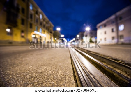 Night highway with rails, the glowing lights of approaching cars. Wide angle view of the level of the rails, in blue tones - stock photo