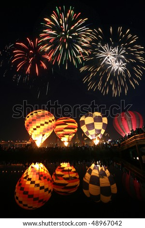 Night hot air balloons glow reflected in the water with beautiful fireworks in the sky