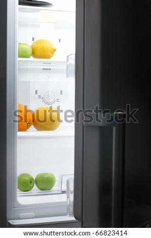 Night Hunger: fridge with fruits in dark room - stock photo