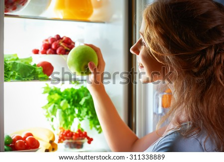 night hunger. Woman in the dark at the open refrigerator - stock photo