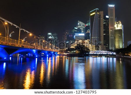 Night illuminated skyline view with water reflections, Singapore - stock photo