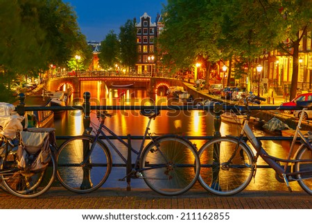 Night  illumination of Amsterdam canal and bridge with typical dutch houses, boats and bicycles, Holland, Netherlands. - stock photo