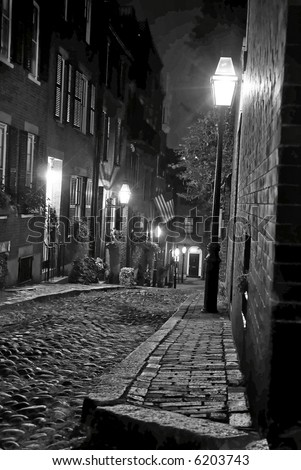night image of an old 19th Century cobble stone road in Boston Massachusetts, lit only by the gas lamps revealing the shuttered windows and brightly lit doorways of the rowhouses on Acorn Street - stock photo