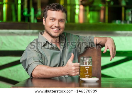 Night in bar. Portrait of cheerful men drinking beer at the bar - stock photo