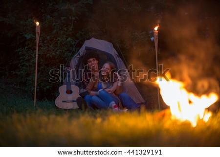 Night in camp. Happy couple. Romantic atmosphere. High ISO, grainy image. - stock photo
