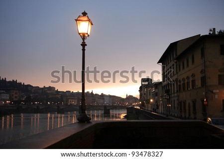 Night in Florence. Glowing vintage street lamp on background with Arno river - stock photo