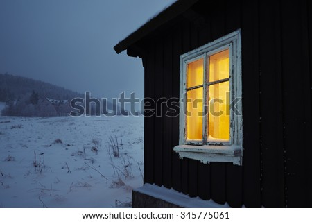 Night in mountains - wooden house in winter landscape  - stock photo