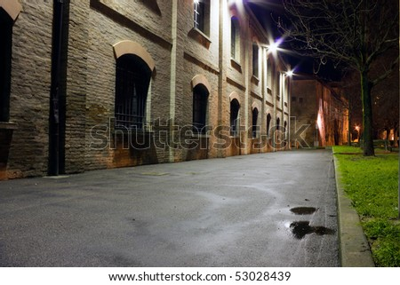 night in the old town, dark street and old industrial buildings - stock photo