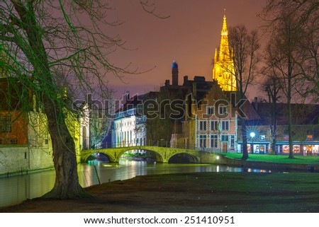 Night landscape at Lake Minnewater with church and bridge in Bruges, Belgium - stock photo