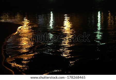 night landscape, sea, colored lights reflected in water