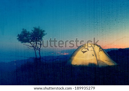 Night landscape with a tent in the mountains. The light from the lantern in a tent. Camping in the countryside. Crimea, Ukraine, Europe. Filtered image: vintage, grunge and texture effects - stock photo