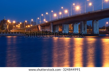 Night landscape with bridge through the river.