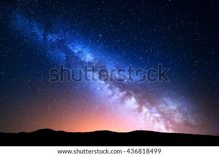 Night landscape with colorful Milky Way and yellow light at mountains. Starry sky with hills at summer. Beautiful Universe. Space background - stock photo