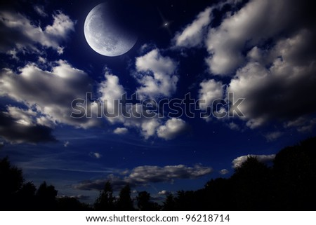 Night landscape with the moon in a cloudy sky above dark forest