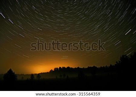 Night landscape with traces of the stars in the night sky on background of a dark forest, fields and mist - stock photo