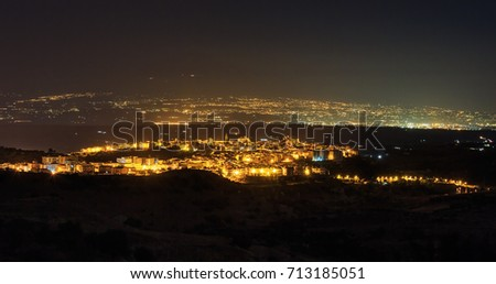 Night Lentini town view in direction from mountain road to sea and Etna volcano (Siracusa, Sicily, Italy)