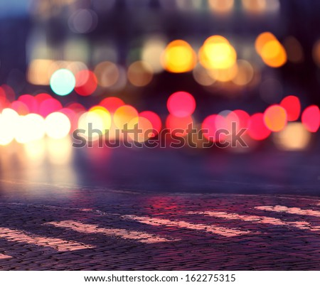 night lights in city and zebra crossing on pavement - stock photo