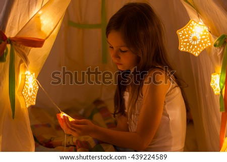 Night. Little girl in a tent holding a star. House. Lighting - stock photo