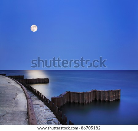 Night Meets Day As A Twilight Moon Spills Yellow Sunlight Down Over Dark And Serene Lake Michigan Waters At The Point Betsie Lighthouse Seawall Just Before Sunrise, Michigan's Lower Peninsula, USA - stock photo