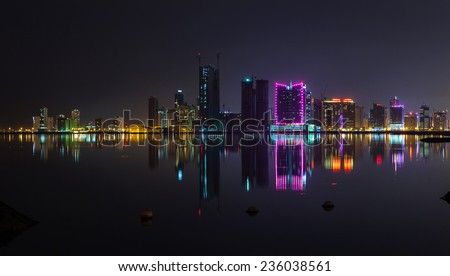 Night modern city skyline panorama with shining neon lights and reflection in the water. Manama, the Capital of Bahrain, Middle East - stock photo
