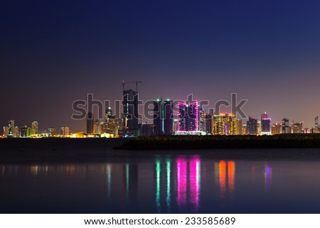 Night modern city skyline with shining lights and reflections in the water. Manama, the Capital of Bahrain, Middle East - stock photo