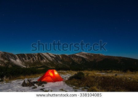 Night mountain landscape with illuminated tent Silhouettes of snowy mountain peaks and edges night sky with many stars and milky way on background illuminated orange tent on foreground - stock photo
