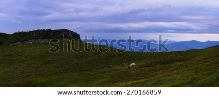 Night mountains landscape with yellow flower meadow hills and slopes and base camp and cloudy sky - stock photo