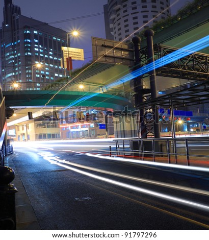 Night move light trails on the modern building background in Highway - stock photo