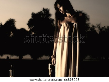 Night of elegance and style. With girl that is standing in this mysterious beach. - stock photo