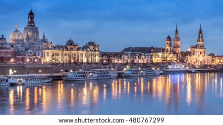 Night panorama of Dresden Old town with reflections in Elbe river and passenger ships. This image is toned.