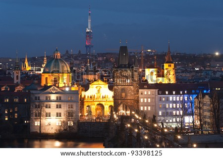 Night panorama of Prague old town with the Charles bridge and the modern Zizkov Tower behind, Czech Republic. - stock photo
