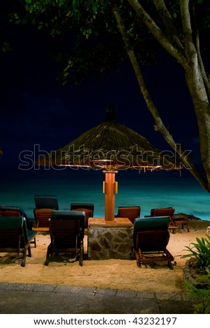 Night paradise beach with deck chair and umbrella in Bali - stock photo
