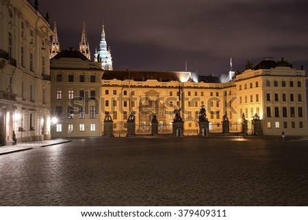 Night Picture of the main entrance to the Prague castle in Prague in Czech Republic. Gate of giants, with baroque statues on the top of pilots. Buildings of the caste are residence of czech president. - stock photo