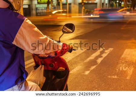 night picture with small depth of field of a scooter rider waiting at the traffic lights - stock photo
