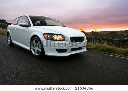 Night Rider, Sports coupe at Sunset. Taken with wide angle Lens - stock photo