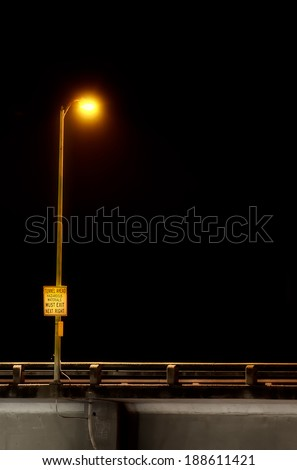 Night scene close up side view of a highway and guardrail, illuminated street light and a warning sign against a black sky background. Copy space for text on black. - stock photo