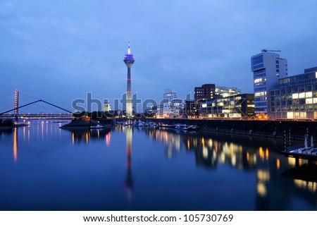 Night scene in Duesseldorf at the Rhine river with the Rheinturm Tower, toned image. - stock photo